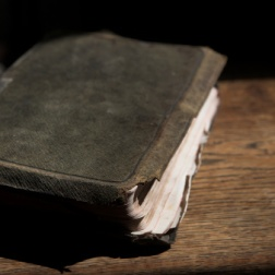 Leather covered old bible lying on a wooden table in a beam of sunlight (not an isolated image) Shallow Depth of field – Focus on closest edge of bible